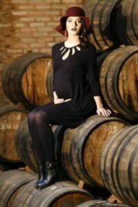 gravid kvinna sitter på vintunna