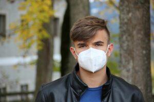 Ung man som bär munskydd