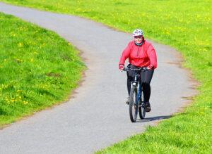 Överviktig kvinna som cyklar